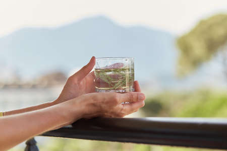 Girl holds in her hands a glass of homemade cocktail with herbs in front of mountains. Summer wallpaper close up.