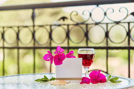 Glass of red wine, pink flowers of bougainvilleaon garden background. Mock up of postcard or invitation. Copy space Banque d'images