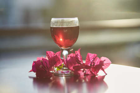 Glass of red wine on blurred mountain background. Decorations of pink bougainvillea flowers with sunlight. Blue hour photography. Romantic dinner concept. Copy space.