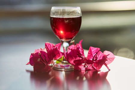Glass of red wine on blurred mountain background. Decorations of pink bougainvillea flowers. Blue hour photography. Copy space.