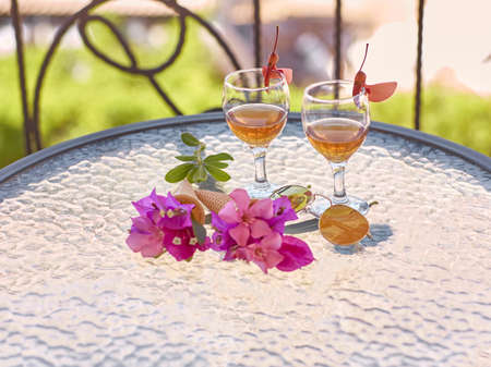 Summer creative surreal flowers and homemade drink liquor on glass table in sunny summer day at the balcony. Romantic dinner. Summer bright background with copy space. High quality photo