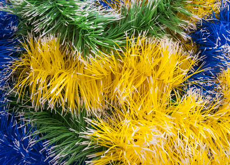 the tinsel: Intertwined Christmas tinsel yellow, green and blue Stock Photo
