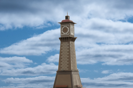 imitations: The round tower with a clock on the background of blue sky with small clouds and benches at the bottom