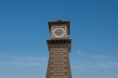 imitations: The round tower with a clock on the background of blue sky with small clouds
