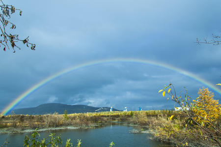 appeared: Rainbow fall, against a background overcast sky, appeared on the lake