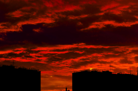 silhouettes of roofs of houses against the background of brightly red evening sky
