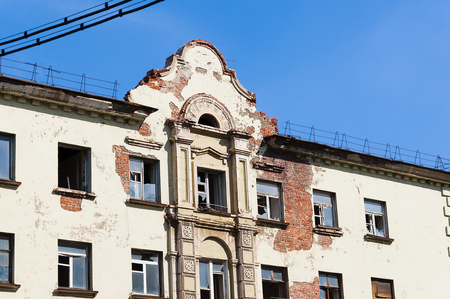Old building with open windows and partially destroyed facade. Elements of ancient architecture.