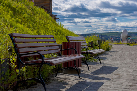 Park benches at the foot of the hill with green grass. Against the blue sky with dark clouds.