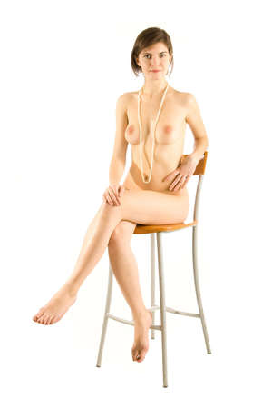 serious naked girl with pearl beads sitting on a chair isolated on white photo
