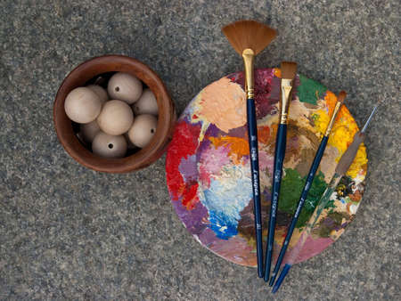 round palette with oil-paint and brushes, and wooden beads in vase on a stone background photo