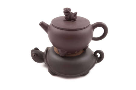 brown ceramic teapot with turtle-shaped stand isolated on white photo