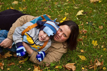 mother and son lying on grass in autumn park photo