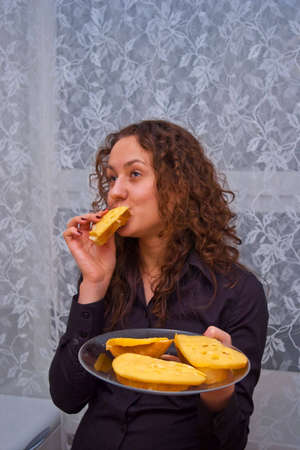 romantic girl with plate of cheese sandwiches eating one of them photo