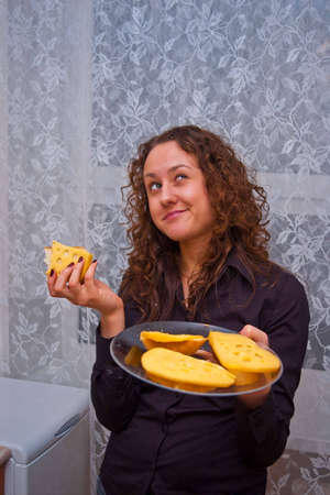 sceptical girl with plate of cheese sandwiches eating one of them photo