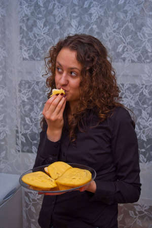 thoughtful girl with plate of cheese sandwiches eating one of them photo