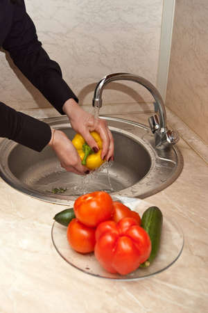close-up of womans hands washing vegetables under a stream of water photo
