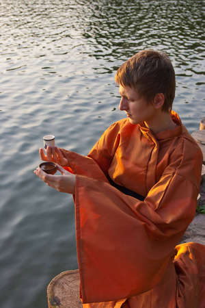 master of tea ceremony with cup in hands near the water photo