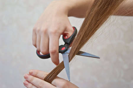 close-up of cutting lock of hair with scissors photo