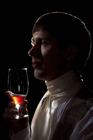 dandy with glass of wine, low key portrait isolated on black photo