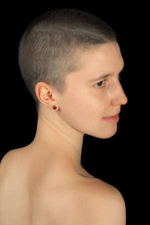 portrait of shaved girl isolated on black photo
