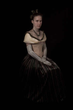 nineteenth: sitting girl in nineteenth century dress isolated on black