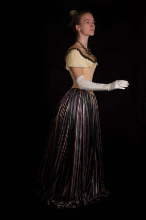 nineteenth: standing girl in nineteenth century dress isolated on black
