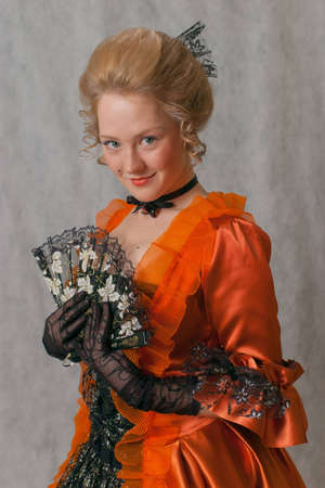 studio shot of a girl in orange baroque dress with lace fan photo