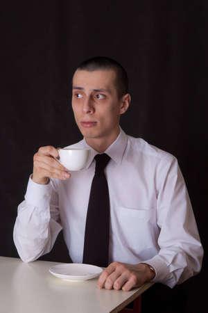 portrait of businessman drinking coffee on black photo
