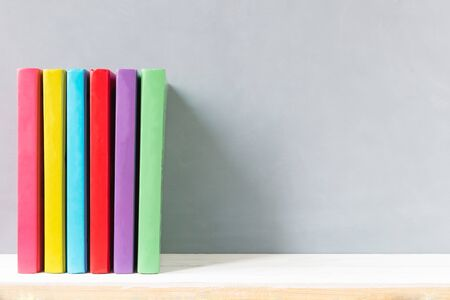 multicolour books on a wooden shelf and gray wall. with copy space