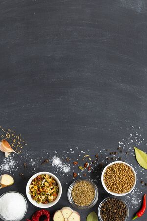 Colourful various herbs and spices and dry vegetable for cooking in wooden spoons and bowls on dark background with copy space. top view. vertical layout 版權商用圖片