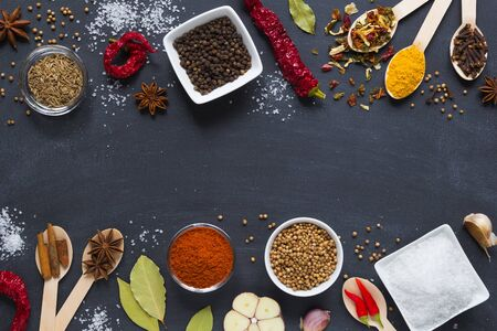 Colourful assorted herbs and spices and dry vegetable for cooking in wooden spoons and bowls on dark background with copy space. top view. Standard-Bild