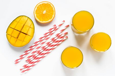 mango orange smoothies in glasses and paper tubes flat lay top view white background