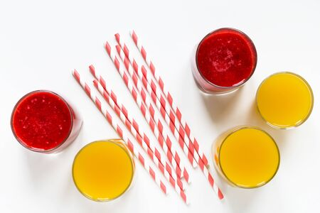 Strawberry mango smoothies in glasses and paper tubes flat lay top view white background