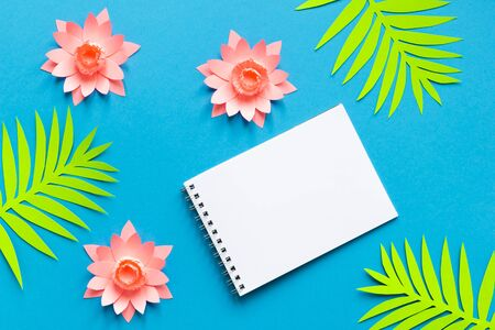 Concept summer background. Notepad and tropical flowers and leaves. Paper art. Top view. Flat lay. copyspace. Empty.