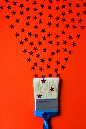 Surreal paint brush drawing red stars confetti. Artistic concept on red paper background