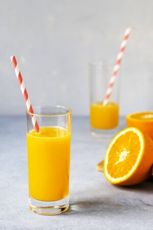 Tall glass of tasty freshly squeezed orange juice standing on table on hot summer day with halved fresh orange. Vertical layout
