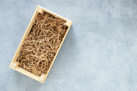 Top view of wooden box for eco gift filled with decorative shredded white paper on gray background copy space flat lay top view.