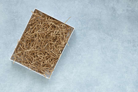 Empty gift box mockup for eco gift filled with decorative shredded paper on gray background.