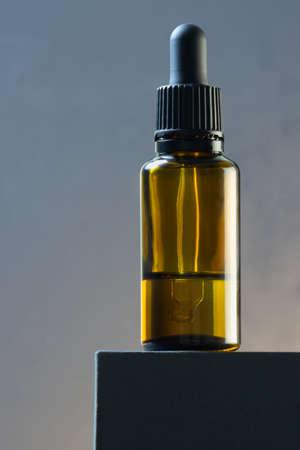 Aromatherapy essential oil dropper bottle on dark podium gray background. Foto de archivo