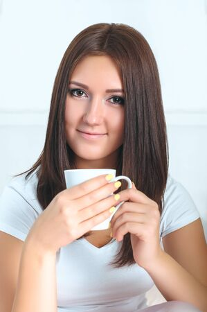 cute girl: Attractive girl in shirt enjoying a cup of coffee.