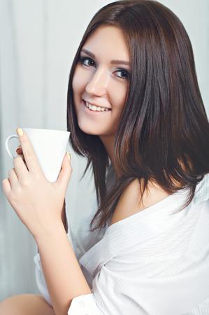Jolie fille en chemise en dégustant une tasse de café.