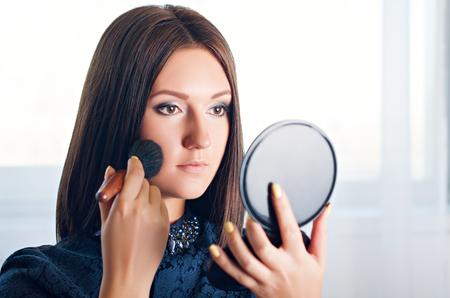 Portrait d'une femme belle application cosmétique, regardant dans un miroir