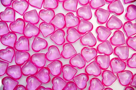 Background of pink, glass hearts on a white background. The concept of Valentine's Day, background, texture.