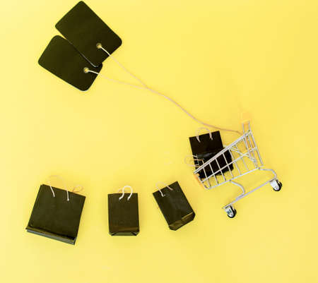 close-up of shopping trolley on yellow background with some copy space creative