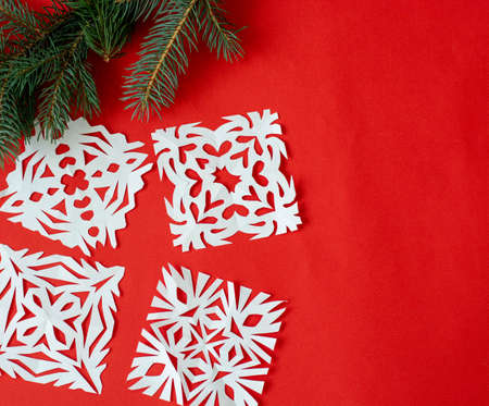 Creative composition of Christmas decoration snowflakes, handmade, on a red background. Festive concert. space for text. Flat lay.