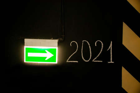 Green emergency exit sign or fire exit sign showing the way to New year 2021, arrow symbol. The concept of Christmas, holiday.