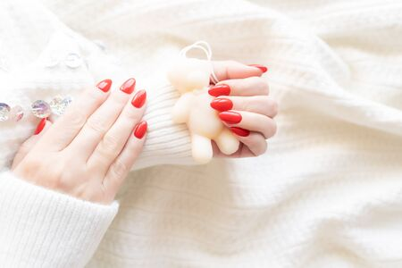 Red fashion manicure on delicate female hands. Hands of a beautiful young woman on a soft white background.