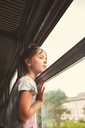 A little girl rides on a train and looks out the open window. A sad look into the distance.
