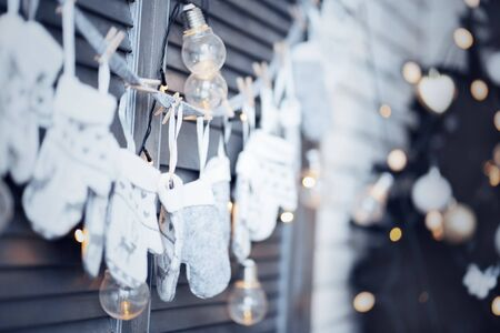 Christmas garland of mittens and lights on a gray wooden background with light bulbs.