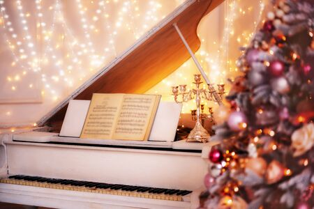 Christmas holiday at home in a cozy atmosphere while playing the piano with candles and decorated fir tree.